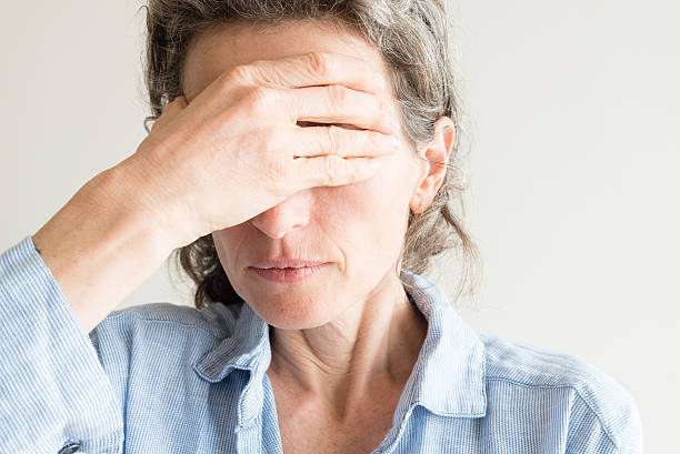 Middle aged woman with hand over eyes stock photo