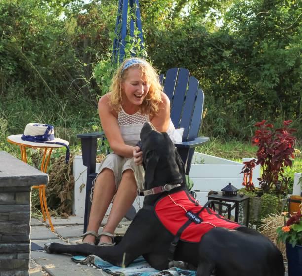 モビリティの問題を持つ中年の女性は、彼女を助ける彼女のグレートデーンサービス犬と屋外で彼女の庭のパティオを楽しむことができます - disabilitycollection ストックフォトと画像