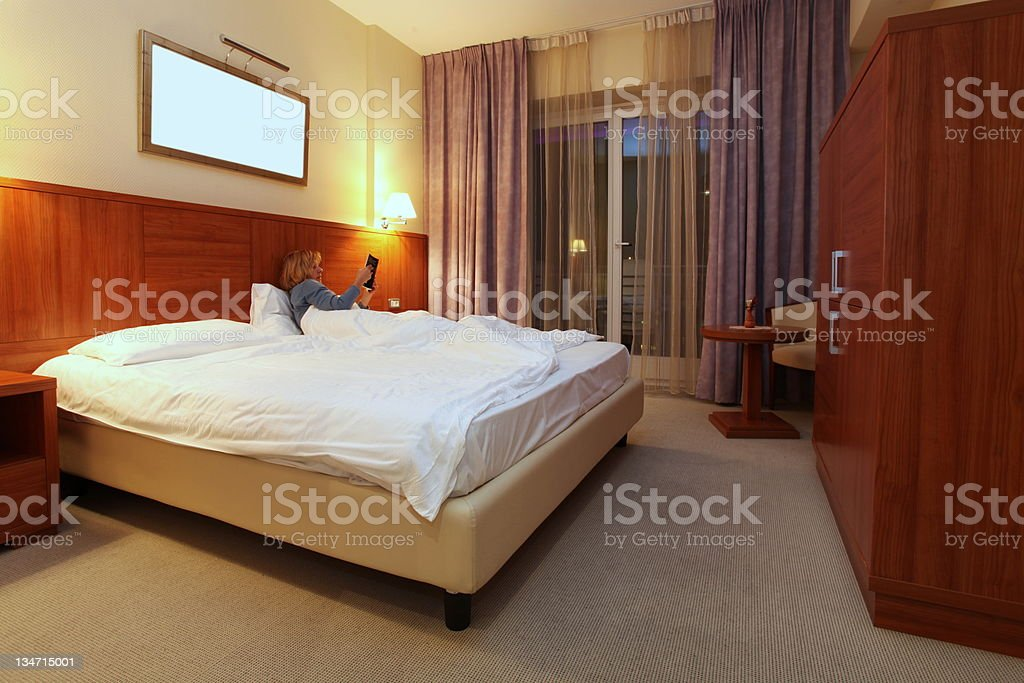 Middle aged women in a hotel room lying in a king sized bed,reading...