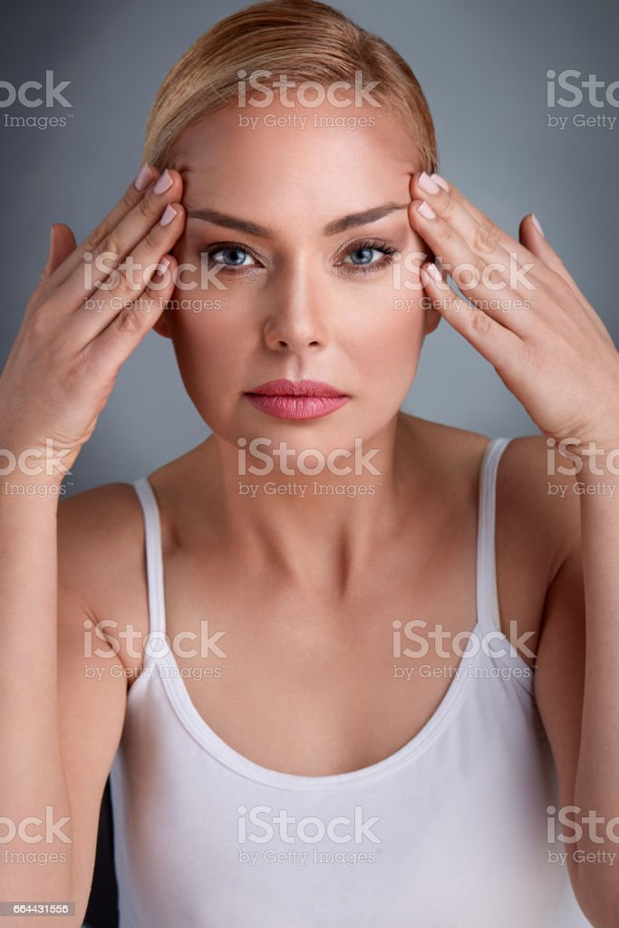 middle aged women looking her face skin stock photo