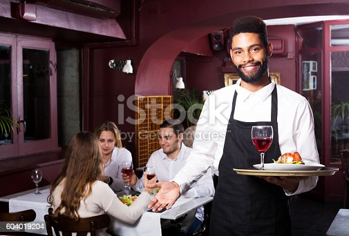 istock Middle class restaurant and cheerful waiter 604019204