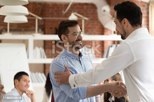 918365170 istock photo Middle east appearance boss praising employee express respect shaking hands 1186603916