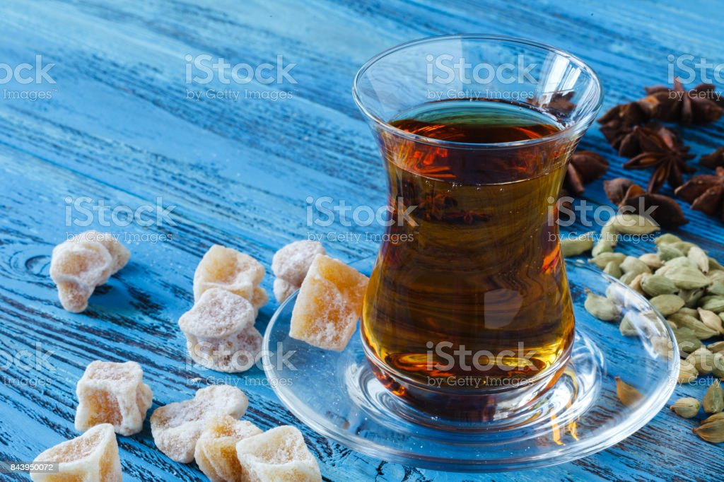 Middle East Black tea with thyme, ethnic glass and glass teapot, vintage wood background stock photo