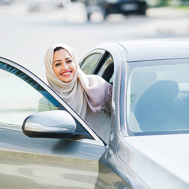 Middle easter woman entering a luxury car in Dubai stock photo