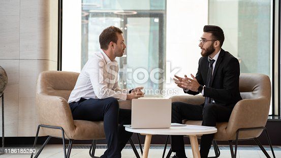 Middle eastern and caucasian ethnicity businessmen seated on armchair in modern office talking solve common issues, banker telling to client regarding bank services make recommendations and consulting
