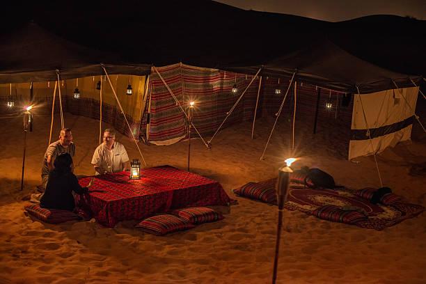 nahöstliche und multi-ethnischen freunde genießen ein gespräch im wüsten-camp - dubai urlaub stock-fotos und bilder