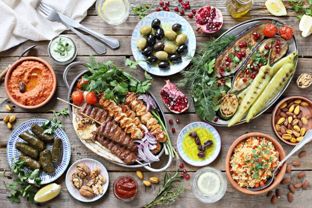 middle eastern, arabic or mediterranean dinner table with grilled lamb kebab, chicken skewers  with roasted vegetables and appetizers variety serving on rustic outdoor table. - mediterranean food imagens e fotografias de stock