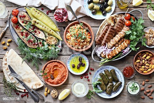 istock Middle eastern, arabic or mediterranean dinner table with grilled lamb kebab, chicken skewers  with roasted vegetables and appetizers variety serving on rustic outdoor table. 950253138