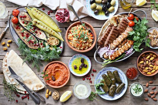 middle eastern, arabic or mediterranean dinner table with grilled lamb kebab, chicken skewers  with roasted vegetables and appetizers variety serving on rustic outdoor table. - lebanon zdjęcia i obrazy z banku zdjęć