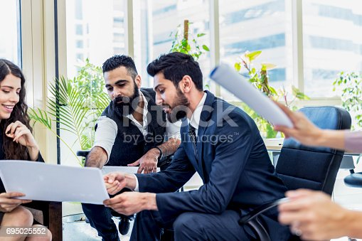 istock Middle Eastern business executives huddling over a brainstorming session 695025552