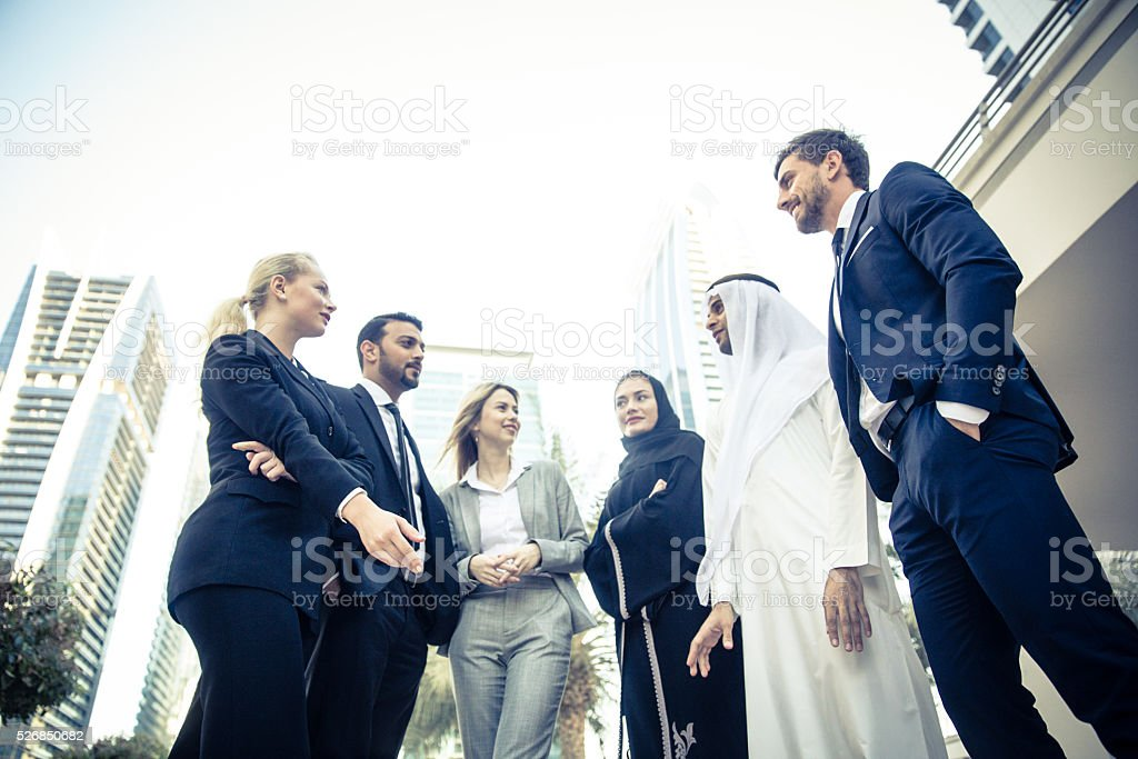 Middle Eastern Business Men Talking with Foreign Expats stock photo