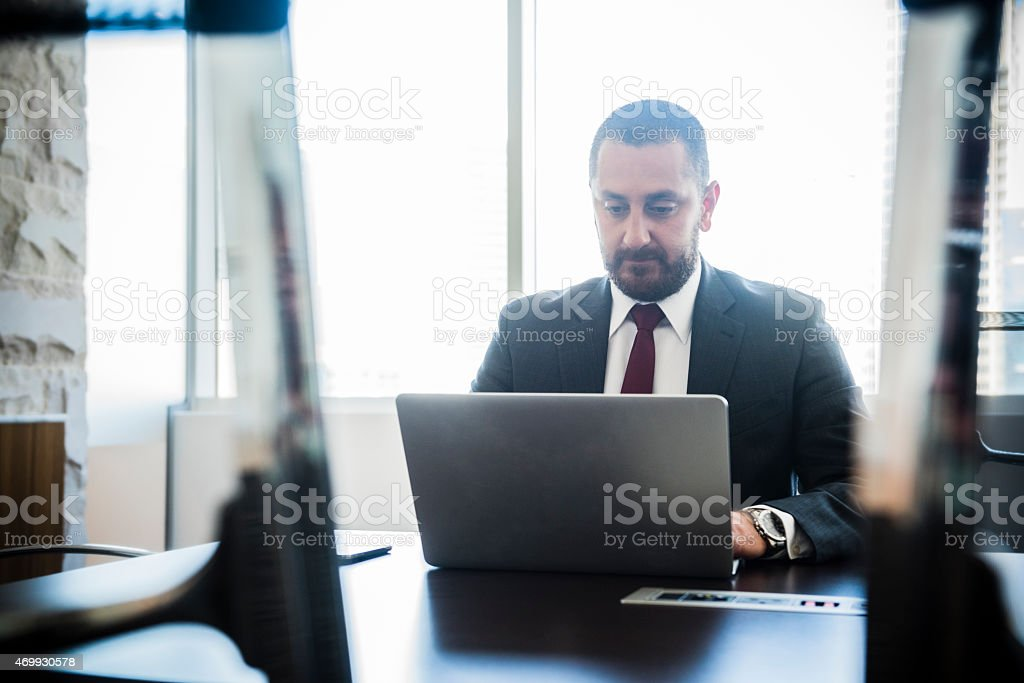 Middle Eastern businessman at work on laptop stock photo