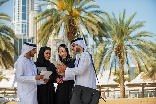 471250190istockphoto Middle Eastern Businessmen and Businesswomen Reviewing Computer Tablet, Dubai, UAE 497357498