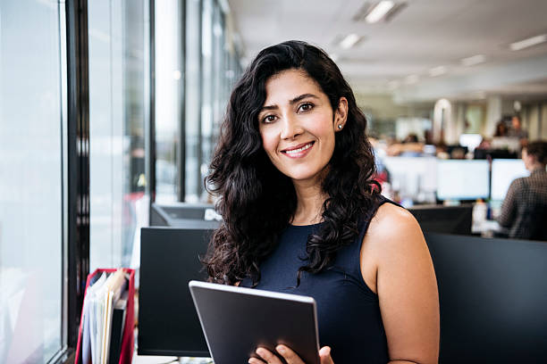 Middle Eastern businesswoman with tablet smiling towards camera stock photo