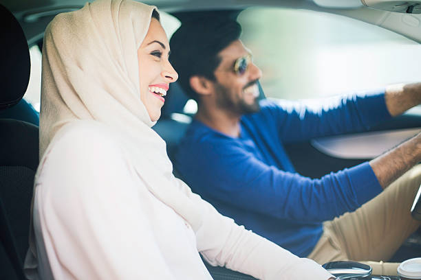 Middle eastern couple driving a luxury car in Dubai stock photo