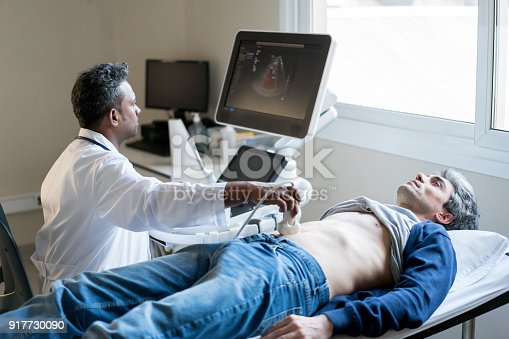 Middle eastern doctor doing a ultrasonography on a male patient at the hospital