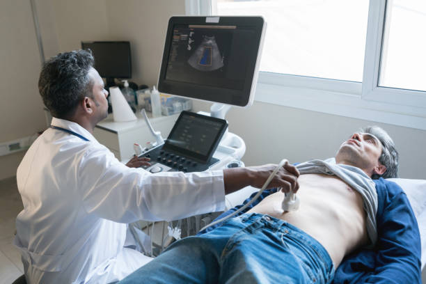 Middle eastern doctor doing an ultrasound scan to a middle aged man stock photo