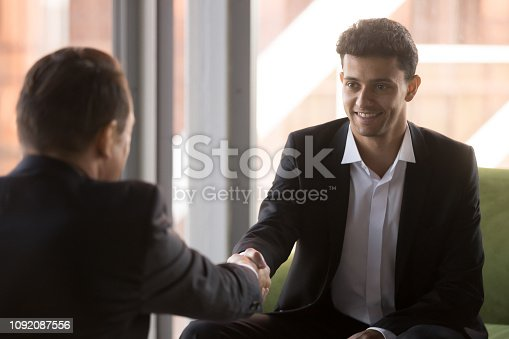 843963182 istock photo Middle eastern ethnicity businessman handshaking with colleague 1092087556