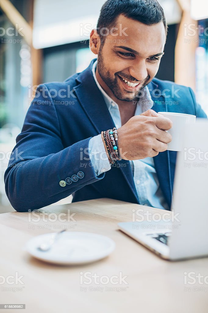 Smiling young Middle Eastern ethnicity man using laptop and drinking...