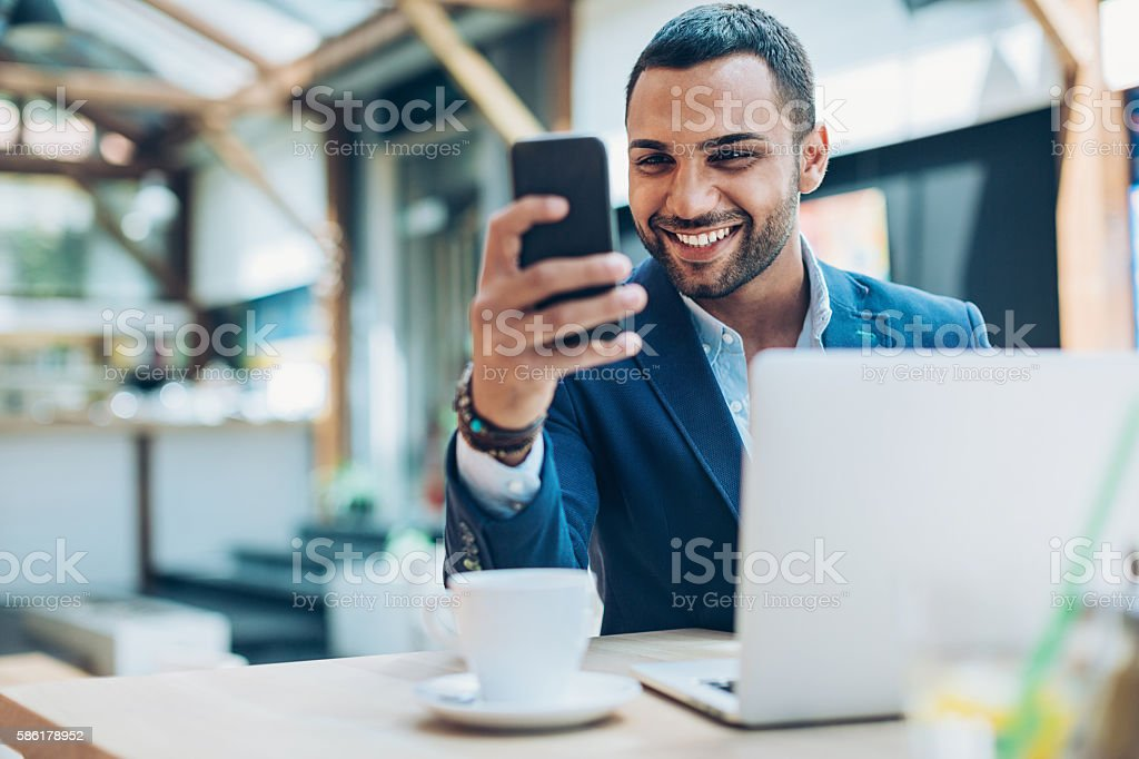 Middle Eastern ethnicity businessman texting in cafe stock photo
