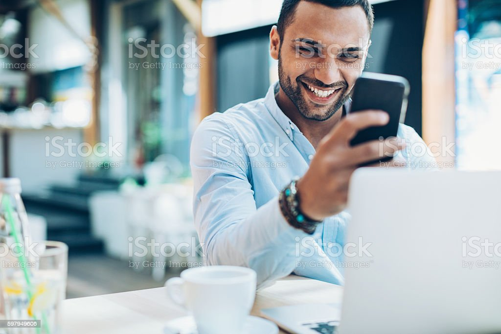 Smiling young man sitting in cafe and checking messages, with his...