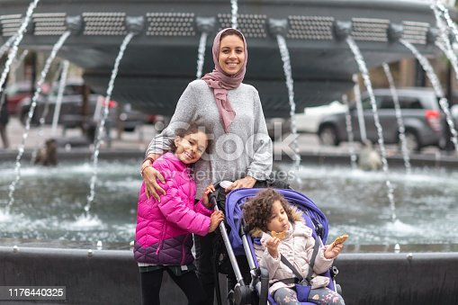 A woman of Middle Eastern descent is spending time with her children. The Muslim woman is posing in front of a fountain in a city park. She is embracing her elementary age daughter. Her younger child is sitting in a stroller. The woman and eldest child are smiling directly at the camera.