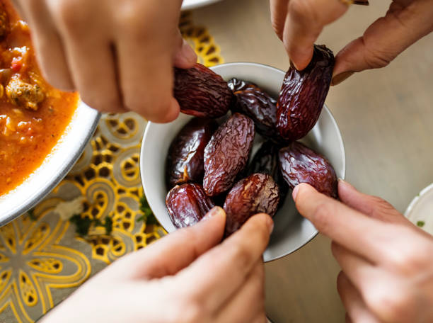 Middle Eastern family sharing and eating dates together stock photo