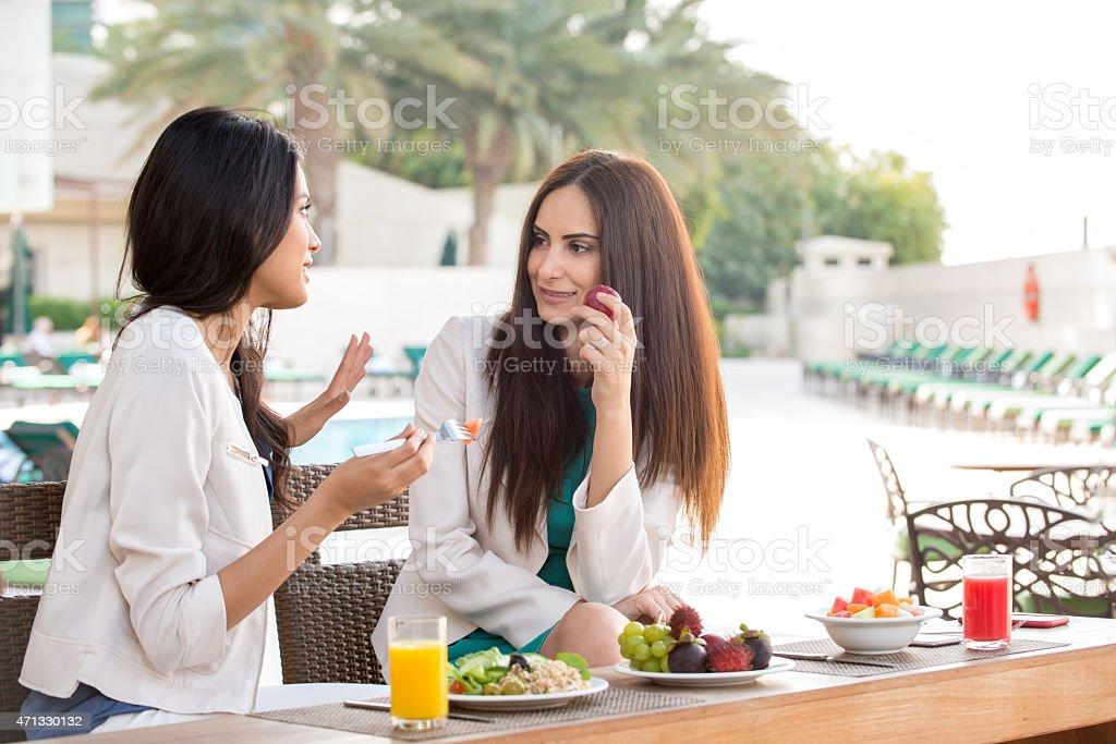 Dubai iStockalypse. Two smiling, attractive Arabian and mixed ethnic...