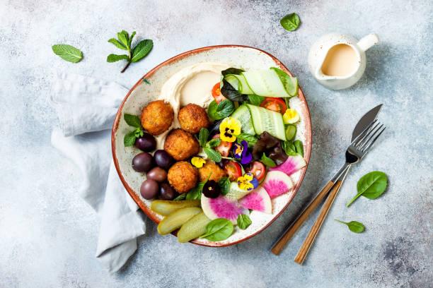 Mittleres Mittagessen Buddha Schüssel mit Hummus, Falafel, Tomaten und Grünsalat, Oliven, Pickles und essbaren Blumen – Foto