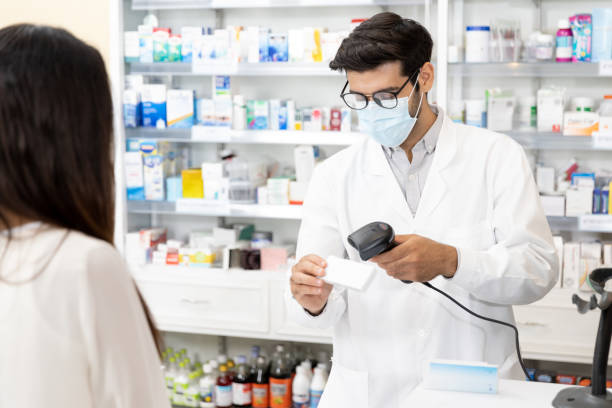 Middle eastern male pharmacist scanning barcode stock photo