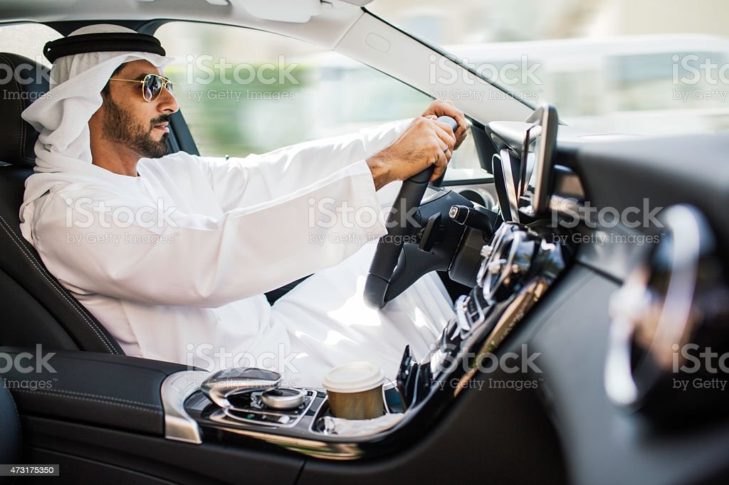 Middle eastern man driving a luxury car in Dubai stock photo