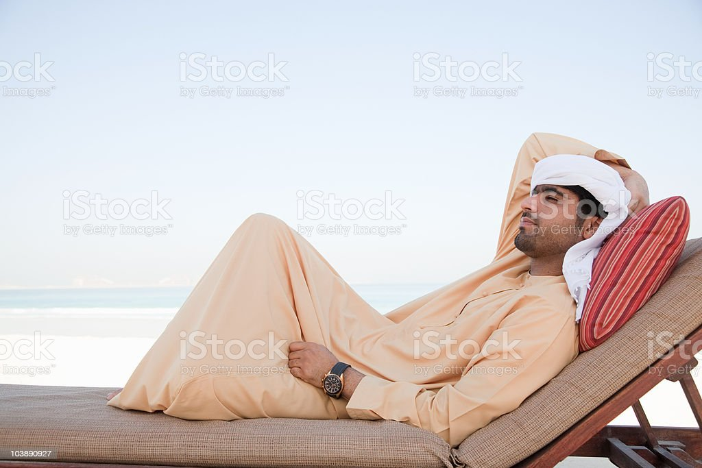 Middle Eastern man relaxing on sun lounger stock photo