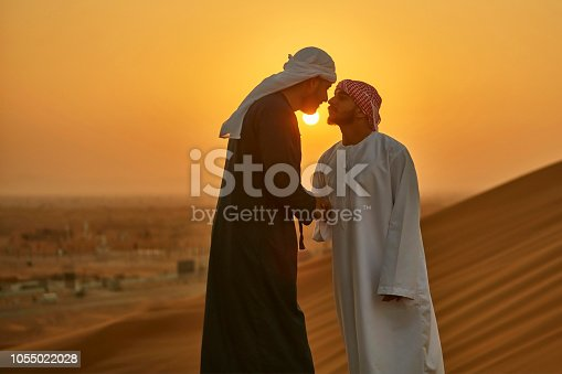 Middle Eastern men greeting in the traditional Arab culture at desert.