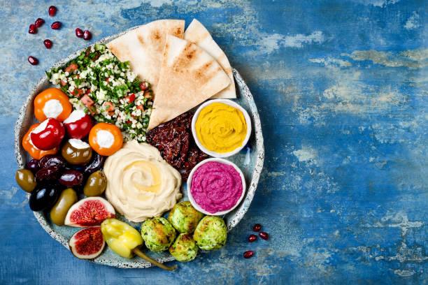 orientalische meze-platte mit grünen falafel, pita, getrockneten tomaten, kürbis und rote beete hummus, oliven, gefüllte paprika, taboulé, feigen. mediterrane vorspeise partyidee - partysalate stock-fotos und bilder