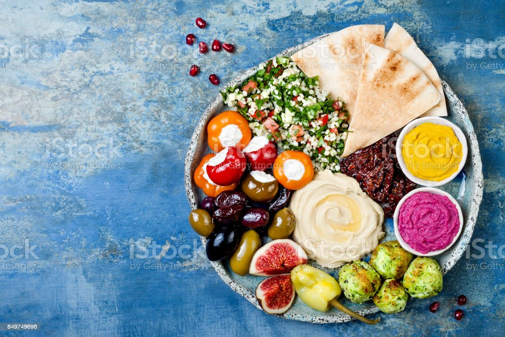Middle Eastern meze platter with green falafel, pita, sun dried tomatoes, pumpkin and beet hummus, olives, stuffed peppers, tabbouleh, figs. Mediterranean appetizer party idea stock photo