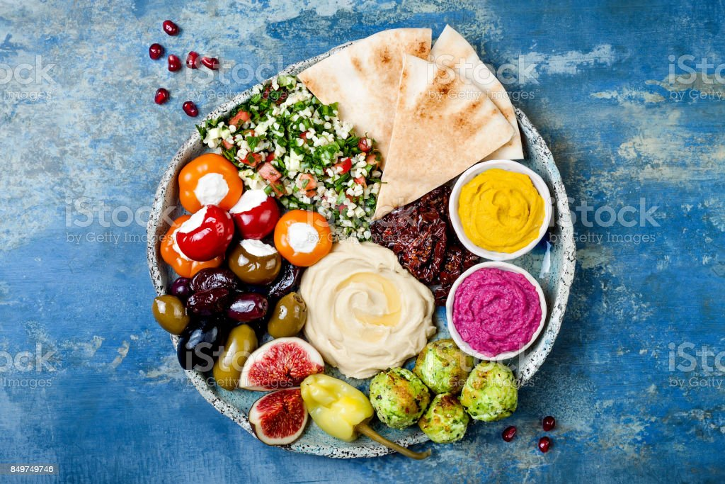 Middle Eastern meze platter with green falafel, pita, sun dried tomatoes, pumpkin and beet hummus, olives, stuffed peppers, tabbouleh, figs. Mediterranean appetizer party idea foto stock royalty-free