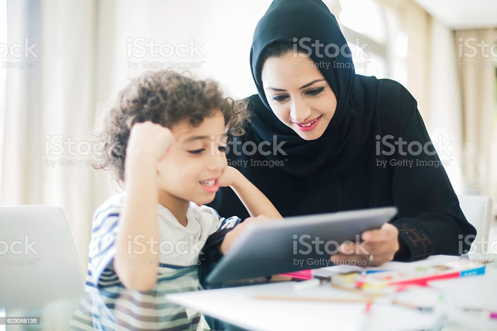 Middle eastern mother helping her child with homework. stock photo