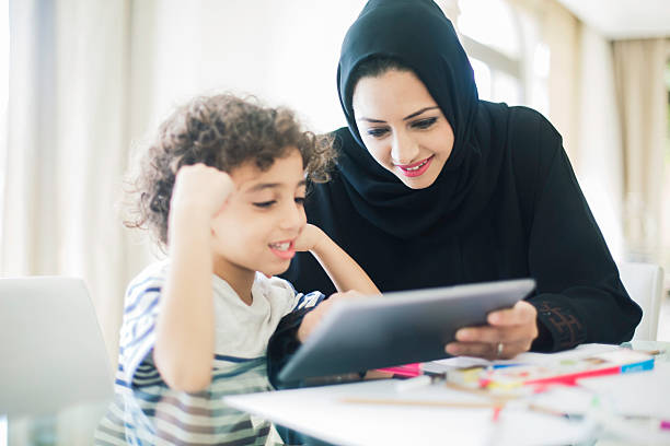 Middle eastern mother helping her child with homework. Middle eastern mother helping her child with homework. old mother son asian stock pictures, royalty-free photos & images