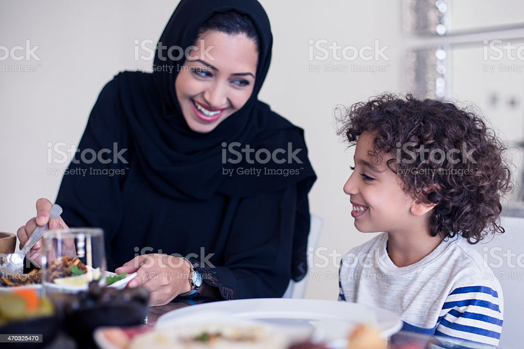 Middle Eastern mother serving food to her son stock photo