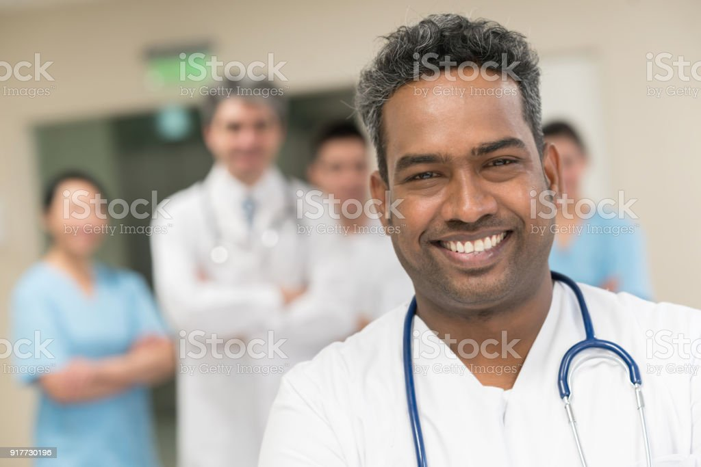 Middle eastern nurse smiling at the camera and a team of physicians standing at the background smiling stock photo