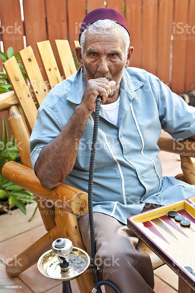 Middle eastern old man smoking hookah royalty-free stock photo