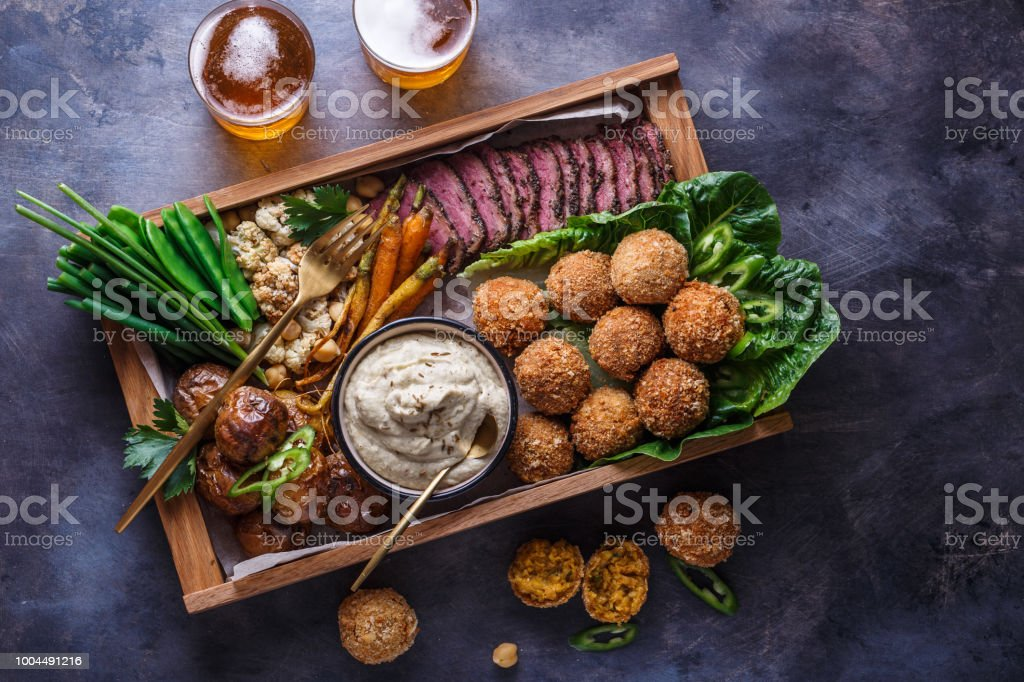 Middle eastern party food: falafel, babaghanoush, potatoes, beef, green veggies. stock photo