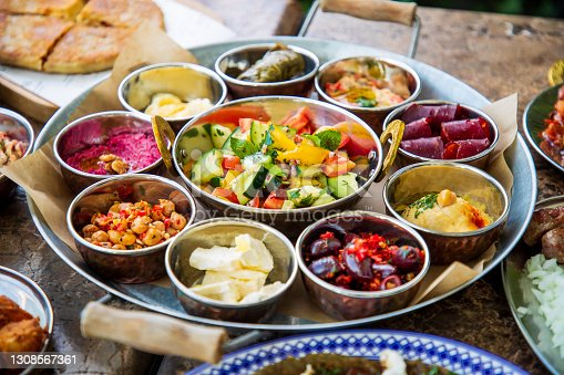 istock Middle Eastern plate with various food in bowls on buffet 1308567361