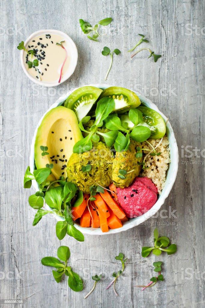 Style moyen-oriental Bouddha le bol vert falafel, quinoa, courge musquée, tomates, avocat, houmous betterave, micro verts et sauce tahiné. - Photo