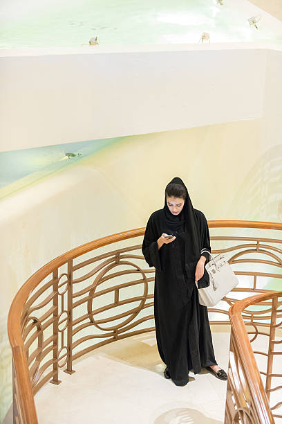 Middle Eastern Woman Checking Cellphone at Luxury Hotel Spa Entrance stock photo
