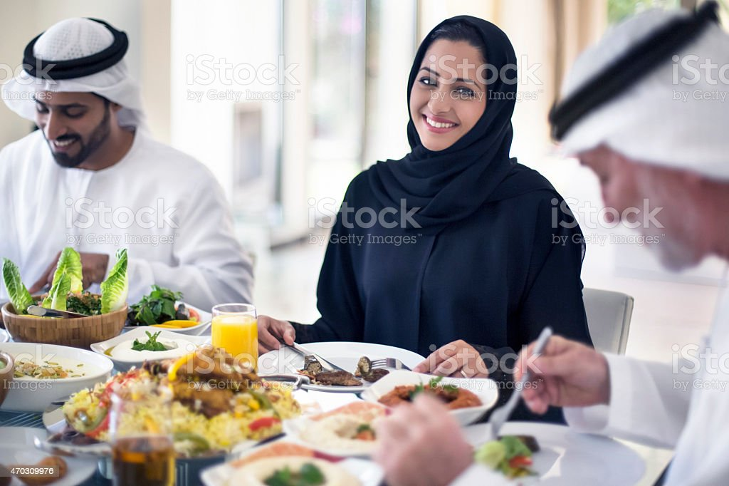 Middle Eastern woman eating with family stock photo