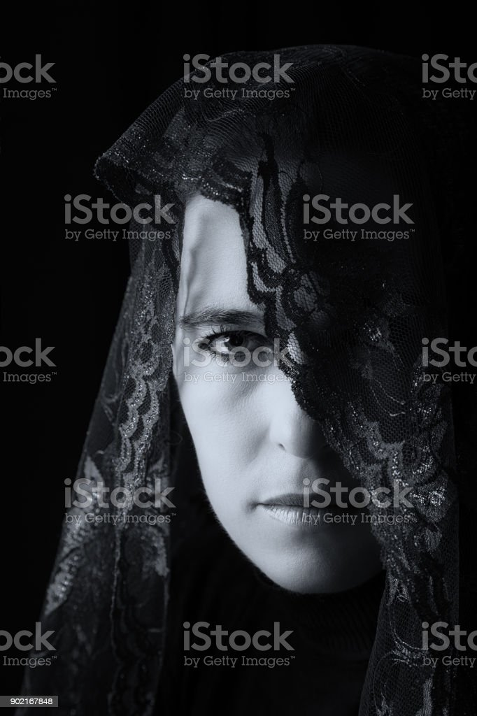 Middle Eastern woman portrait looking sad with a black hijab artistic...