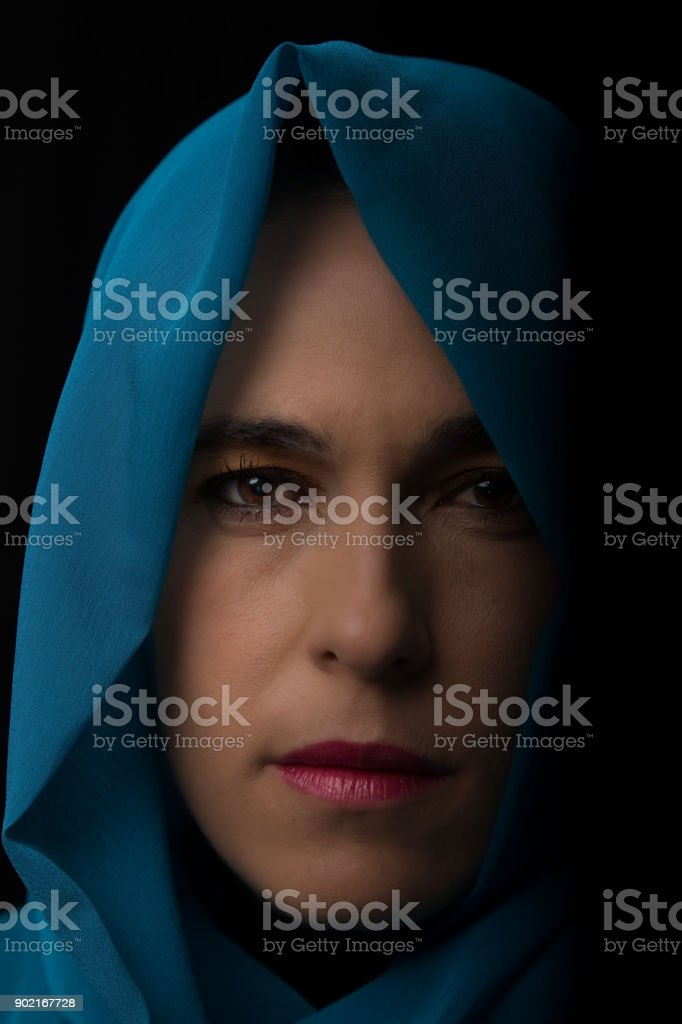 Middle Eastern woman portrait looking sad with a blue hijab artistic conversion stock photo