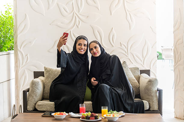 Middle Eastern Women in Abayas Posing for Selfie During Lunch stock photo