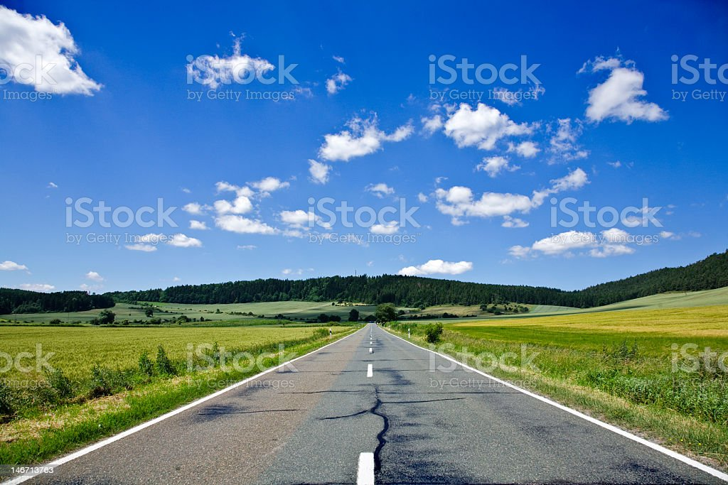 Middle of country highway with grass, hills and blue sky royalty-free stock photo